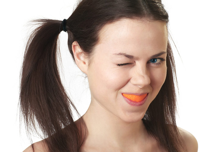 Young woman with an orange peel in her mouth